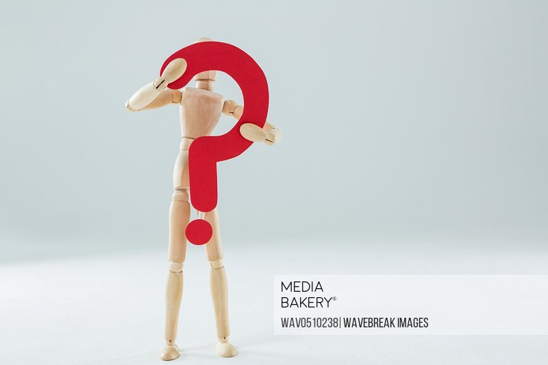 Wooden figurine holding a question mark sign against white background