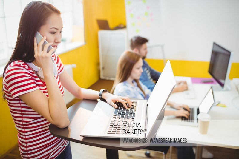 Businesswoman talking on phone while working in creative office against coworkers