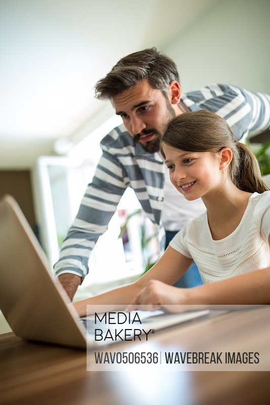 Father and daughter using laptop in the living room at home