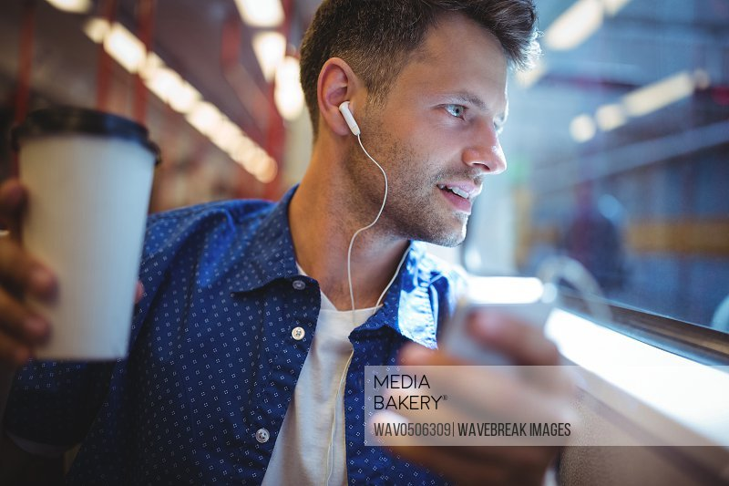 Handsome man listening music on mobile phone while having coffee in train