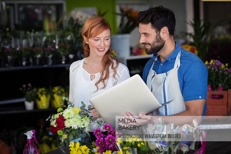 Man showing laptop to woman in the flower shop