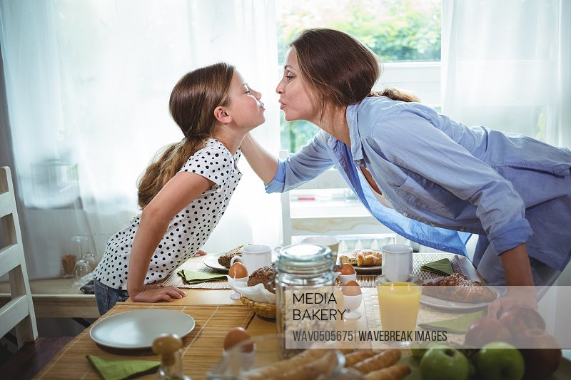 Mother and daughter kissing each other while having breakfast at home