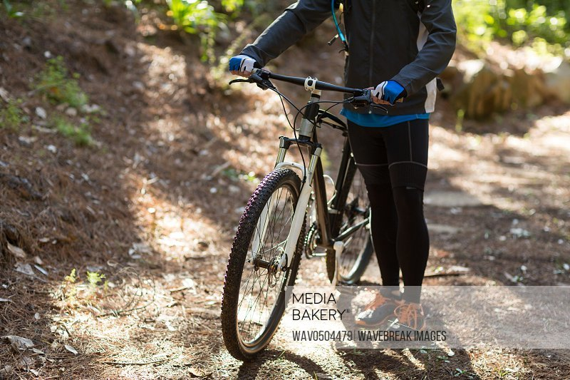 Female biker standing with mountain bike on dirt track in countryside
