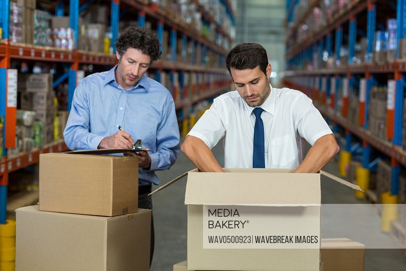 Two warehouse workers checking the boxes in the warehouse