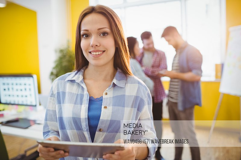 Portrait of smiling businesswoman with digital tablet standing against coworkers in creative office