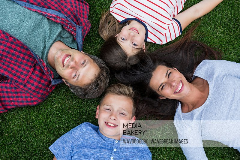 Portrait of happy family lying on grass in park on a sunny day