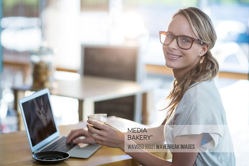 Portrait of woman using a laptop while having cup of coffee in cafe
