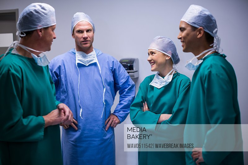 Surgeons having discussion in corridor of hospital