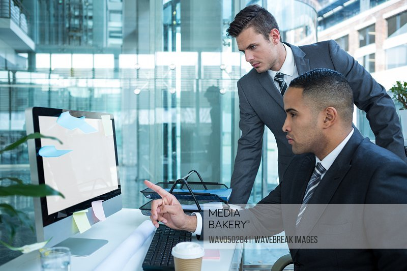 Businesspeople discussing at table over computer in office
