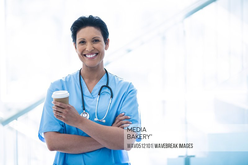 Female nurse standing with disposable cup in corridor of hospital