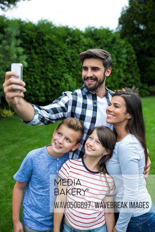 Happy family taking a selfie from mobile phone in park on a sunny day