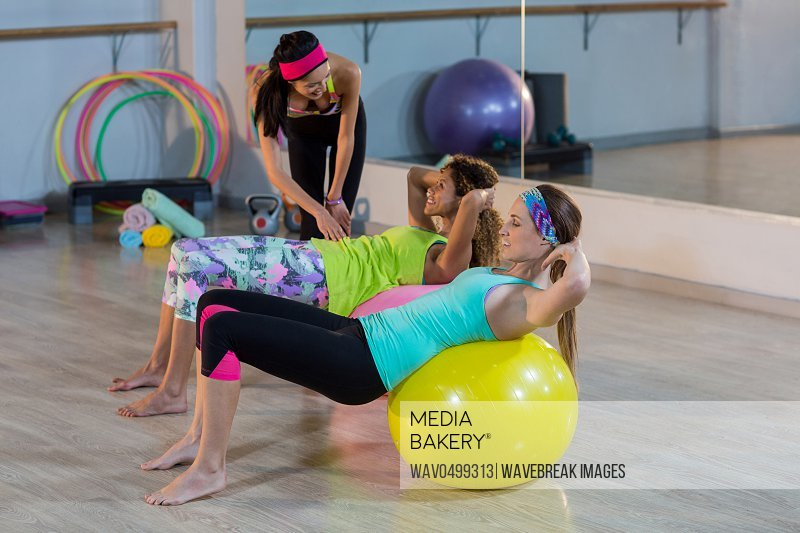 Female trainer assisting woman to exercise on exercise ball in the gym