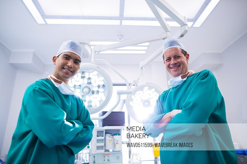Portrait of surgeons standing with arms crossed in operation theater