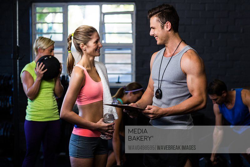 Woman smiling while talking with male trainer in fitness studio