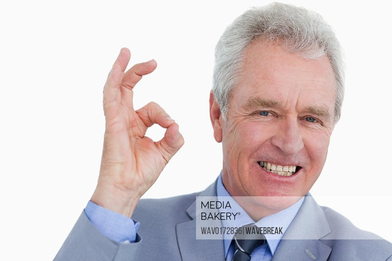 Mature tradesman giving his approval against a white background