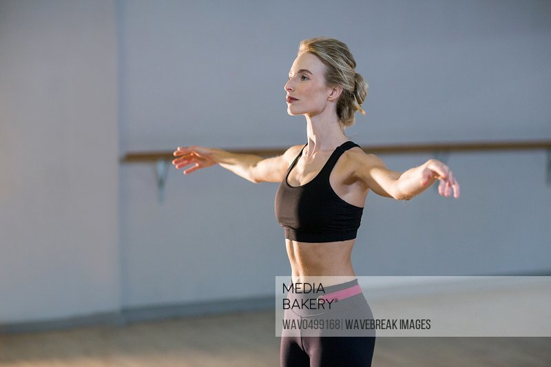 Woman performing stretching exercise in fitness studio