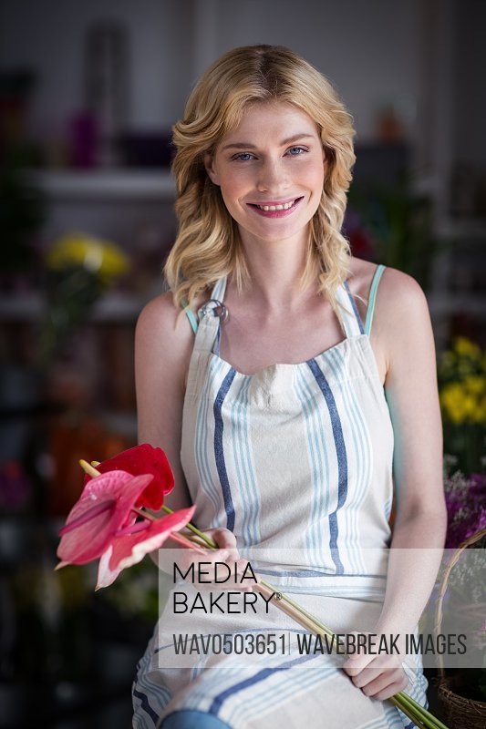 Portrait of smiling female florist holding flowers in the shop