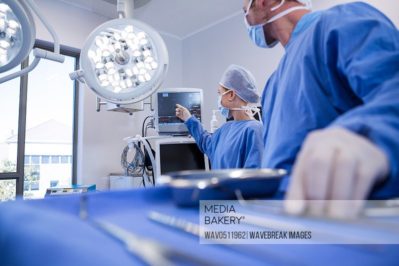 Male and female surgeon using patient monitoring machine in operation theater at hospital
