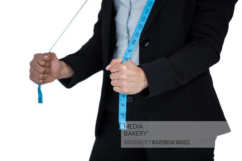 Mid-section of businesswoman holding a measuring tape against white background