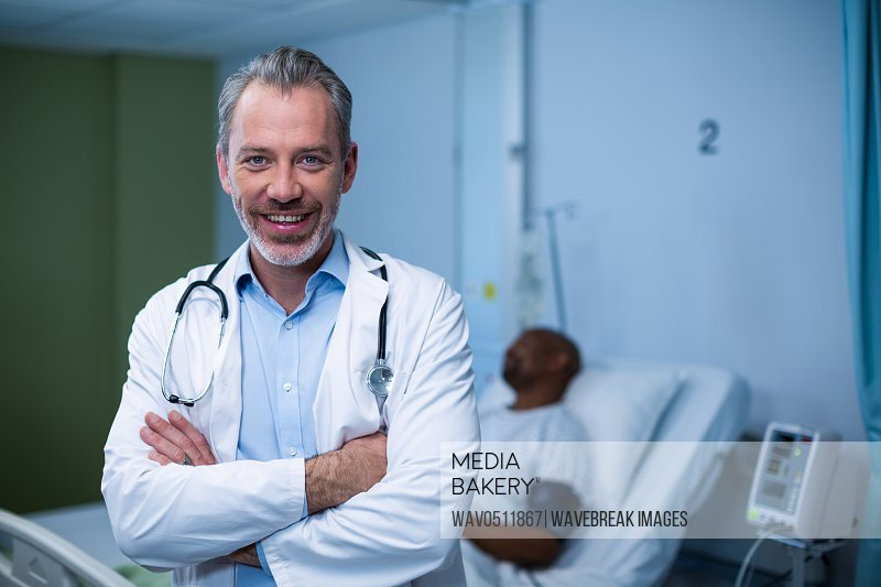 Portrait of doctor standing with arms crossed in ward of hospital