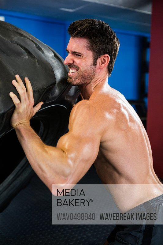 Side view of shirtless male athlete lifting tire in gym