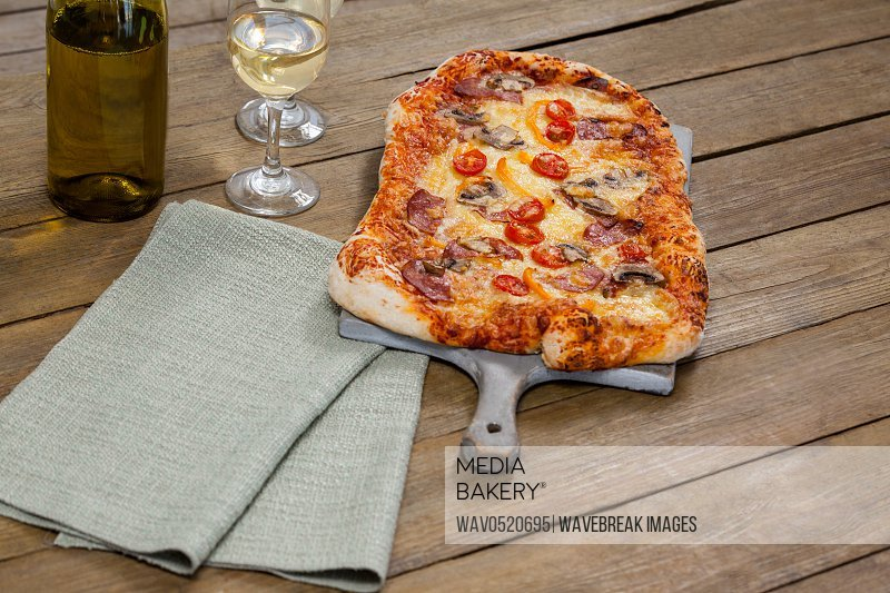 Delicious pizza served on pizza tray with a glasses of wine bottle and wine