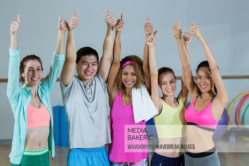 Portrait of group of fitness team showing thumbs up in fitness studio