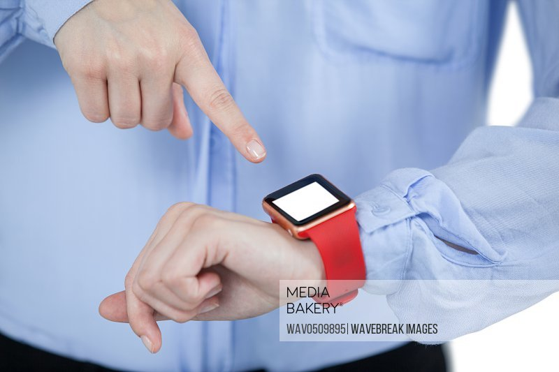 Mid section of businesswoman using smartwatch against white background