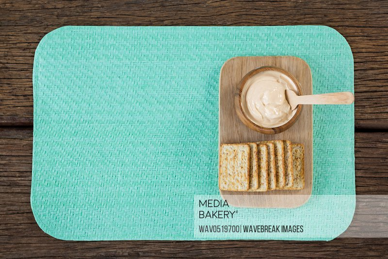 Cheese sauce with bread on serving board