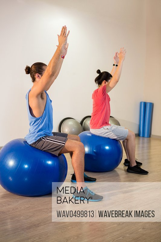 Men performing stretching exercise on exercise ball in gym