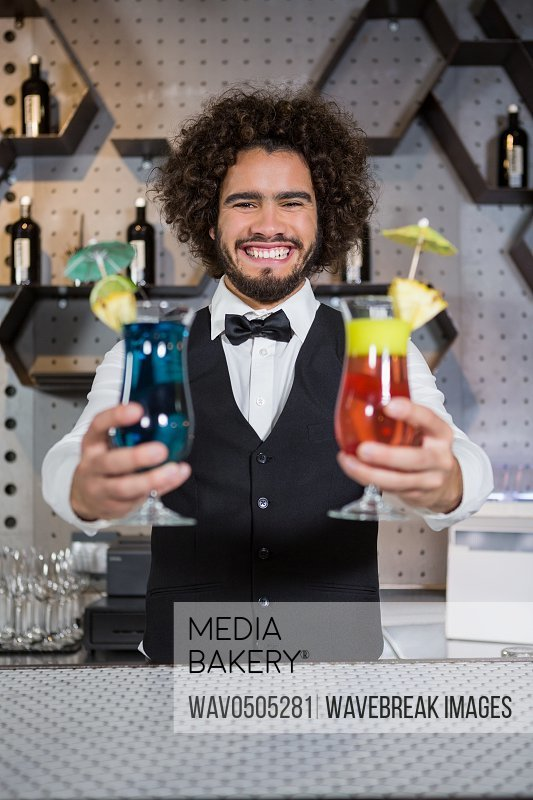 Smiling bartender holding two glass of cocktail in bar counter at bar
