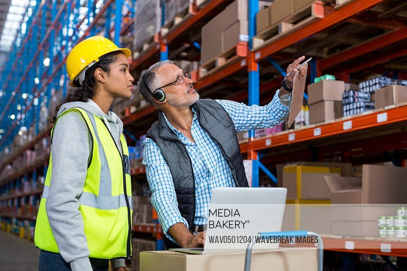 Warehouse manager and female worker interacting while using laptop in warehouse