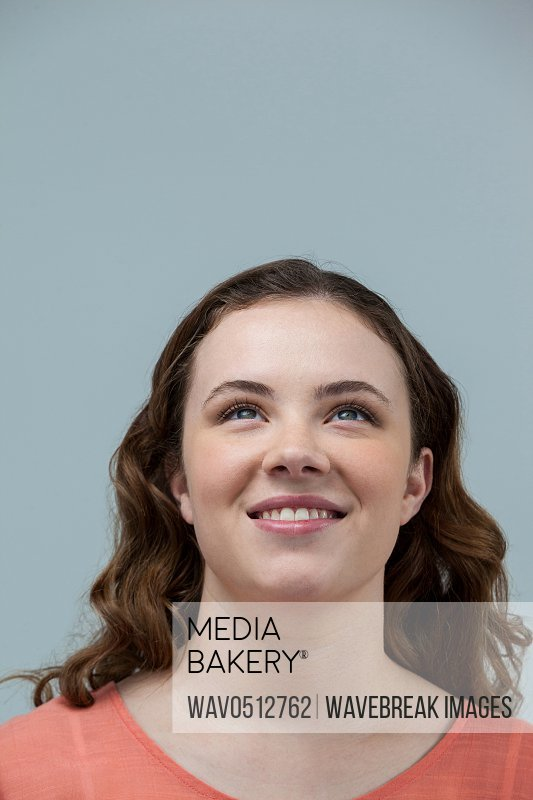 Smiling woman looking upward against grey background