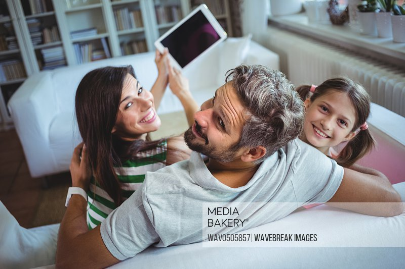 Parents sitting on sofa with daughter and clicking a selfie on digital tablet at home