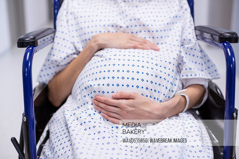 Mid section of pregnant woman sitting on wheelchair