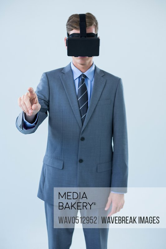 Businessman pointing his finger while using virtual reality headset against white background