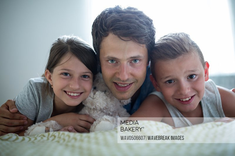 Portrait of father lying with their kids in bedroom at home