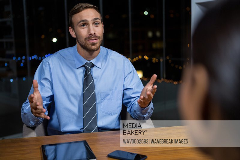 Businessman having a discussion in office at night