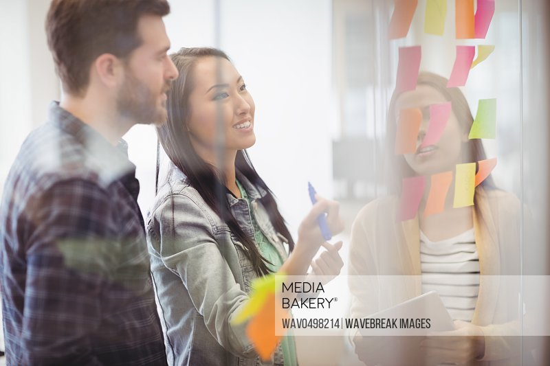 Smiling female photo editor with coworker looking at multi colored sticky notes on glass in meeting room