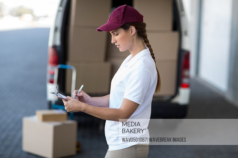 Delivery woman writing on clipboard while standing next to van outside the warehouse