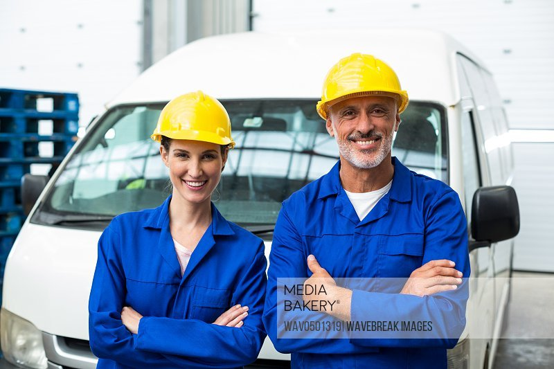 Portrait of warehouse workers standing together with arms crossed in warehouse