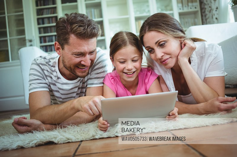 Parents and daughter lying on rug and using digital tablet at home