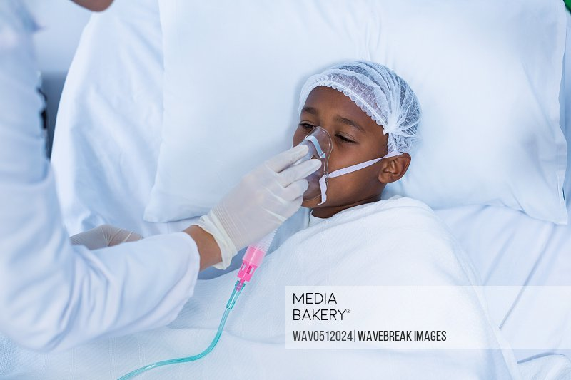 Doctor placing an oxygen mask on patient in hospital