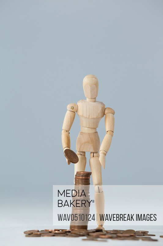 Wooden figurine standing and making stack of coins against white background