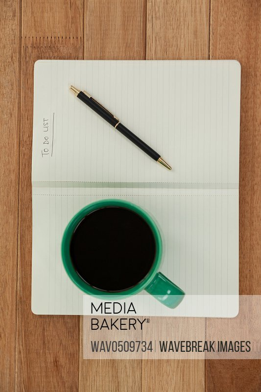 Close-up of coffee mug with diary and pen on wooden table