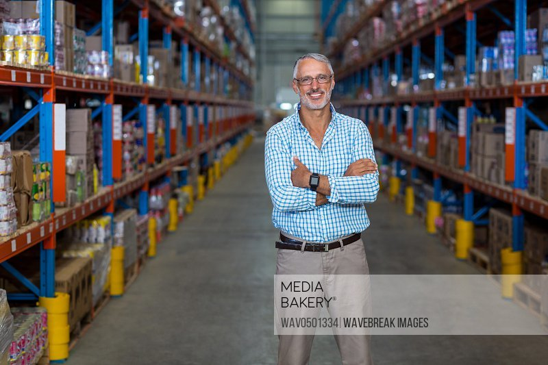 Portrait of warehouse manager standing with arms crossed in warehouse