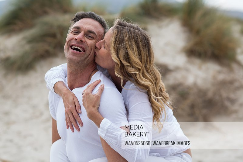 Mature man giving piggyback ride to woman on beach