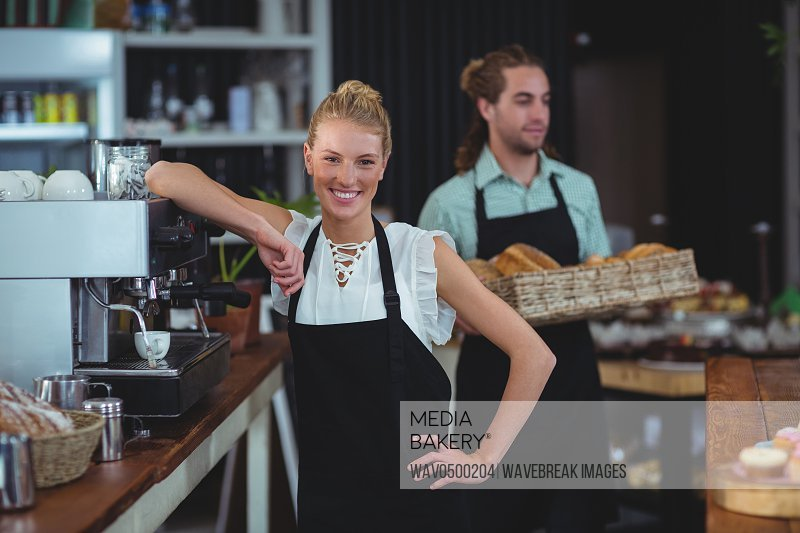 Portrait of smiling waitress standing behind counter in cafe