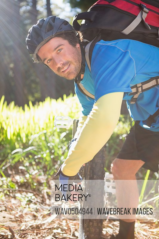 Portrait of male mountain biker fixing his bike chain in the forest