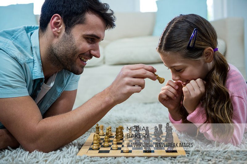 Father and daughter playing chess in the living room at home